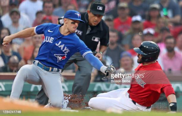 The Red Sox J.D. Martinez beats the throw to Toronto 3B Cavan Biggio as he advances from second base on a bottom of the first inning wild pitch. The...