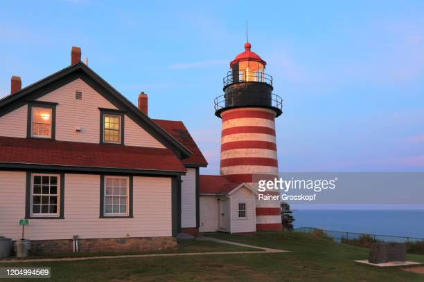 the red-and-white striped west quoddy head lighthouse in maine at sunset - rainer grosskopf fotografías e imágenes de stock