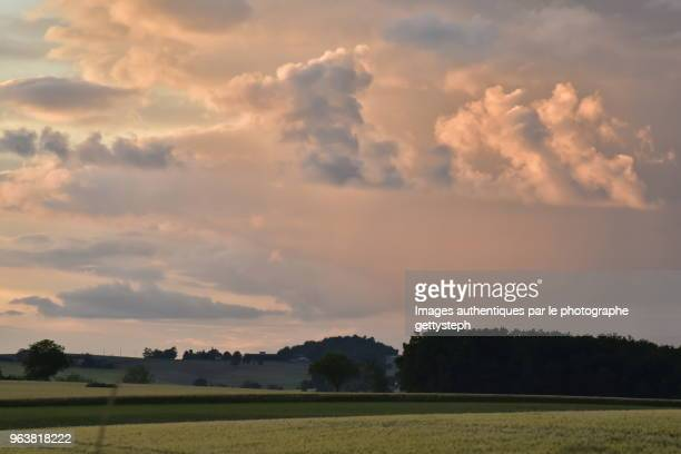 The red-brown clouds above rural landscape