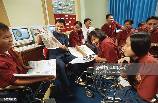 The Redemptorist Vocational School for the Disabled in Pattaya Thailand Picture shows students looking at possible designs they have created for the...