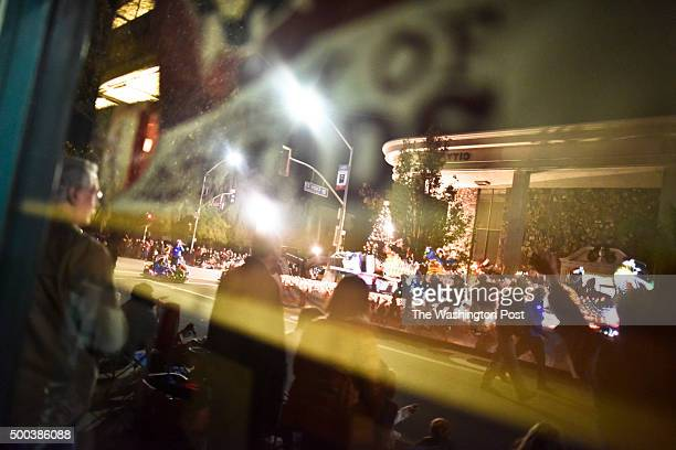The Redlands Christmas Parade and bystanders are reflected in a window along the parade route in downtown Redlands Saturday night. 2015 Redlands...
