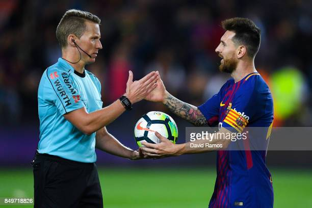 The referee Alejandro Jose Hernandez Hernandez gives the ball to Lionel Messi of FC Barcelona atg the end of the La Liga match between Barcelona and...