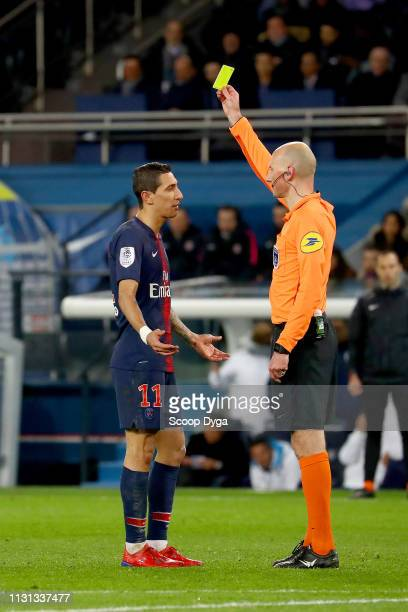 The referee Antony Gautier gives a yellow card to Angel Di Maria of Paris Saint Germain during the Ligue 1 match between Paris Saint Germain and...