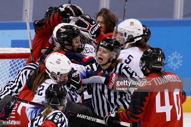 The referee attempts to separate Kelly Pannek of the United States and Blayre Turnbull of Canada late in the game during the Women's Ice Hockey...