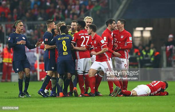 The referee attempts to take control of the players after Emil Forsberg of RB Leipzig fouled Philipp Lahm of Bayern Muenchen and is later sent off...