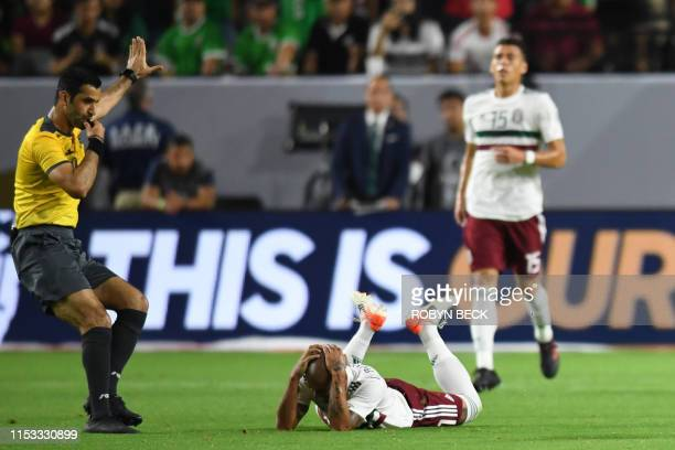 The referee blows his whistle as Mexico's defender Luis Alfonso Rodriguez falls to the pitch with an injury during the 2019 Concacaf Gold Cup...