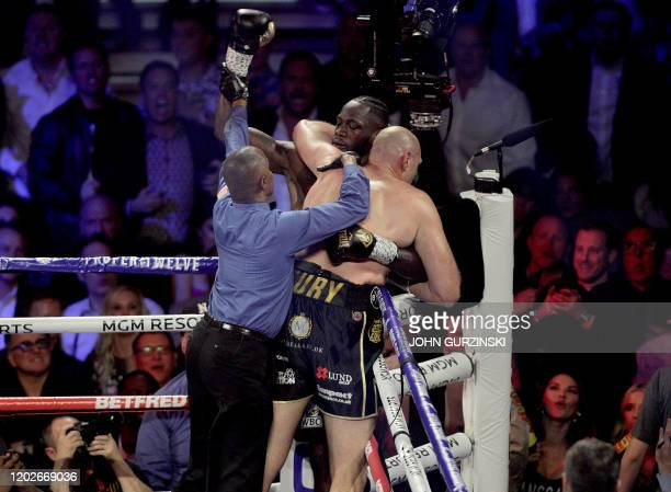 The referee breaks up British boxer Tyson Fury and US boxer Deontay Wilder after clinching in the corner during their World Boxing Council...