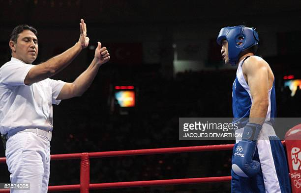 The referee counts over France's Khedafi Djelkhir after being knocked by Ukraine's Vasyl Lomachenko during their Beijing 2008 Olympic Games...