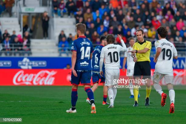 The referee gestures as Real Madrid's Croatian midfielder Luka Modri reacts during the Spanish league football match between SD Huesca and Real...