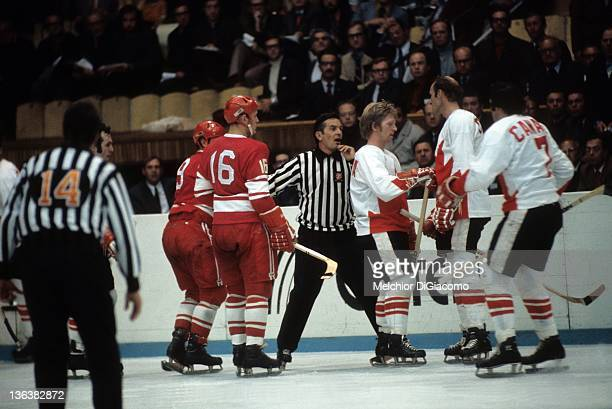 The referee gets in the middle of an arguement between Bill White of Canada and Yuri Blinov of the Soviet Union as Pat Stapleton and Phil Esposito of...