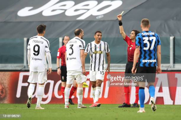 The referee Gianpaolo Calvarese shows a yellow card to Giorgio Chiellini of Juventus following an incident with Romelu Lukaku of Internazionale in...