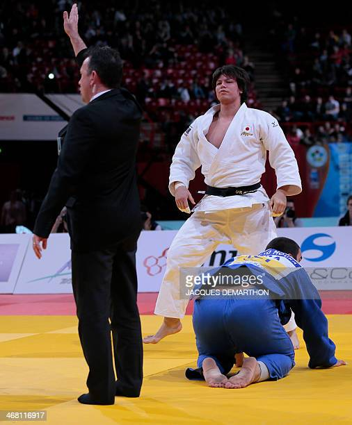 The referee gives the victory to Japan's Shichinohe Ryu against Brazil's David Moura during the men's 100kg final at the 2014 Paris Judo Grand Slam...