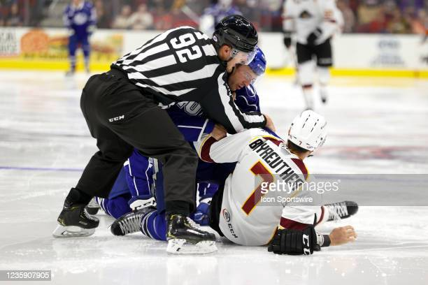 The referee has to separate Syracuse Crunch forward Gabriel Dumont and Cleveland Monsters defenceman Gavin Bayreuther during the first period of the...
