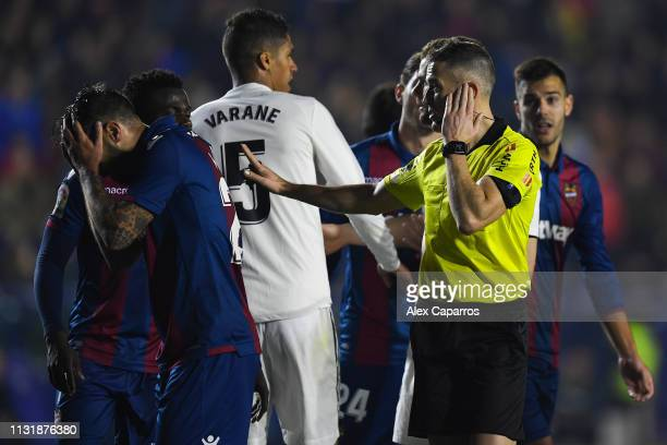 The referee Iglesias Villanueva listens the VAR during the La Liga match between Levante UD and Real Madrid CF at Ciutat de Valencia on February 24...