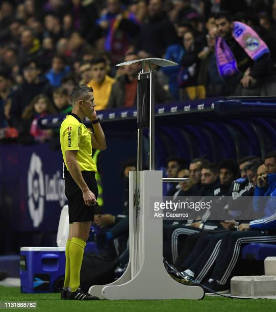 The referee Iglesias Villanueva review an action on the VAR screen during the La Liga match between Levante UD and Real Madrid CF at Ciutat de...