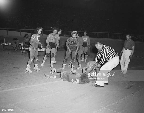 The referee intervenes in an incident during an international roller derby at Harringay Arena London 1953