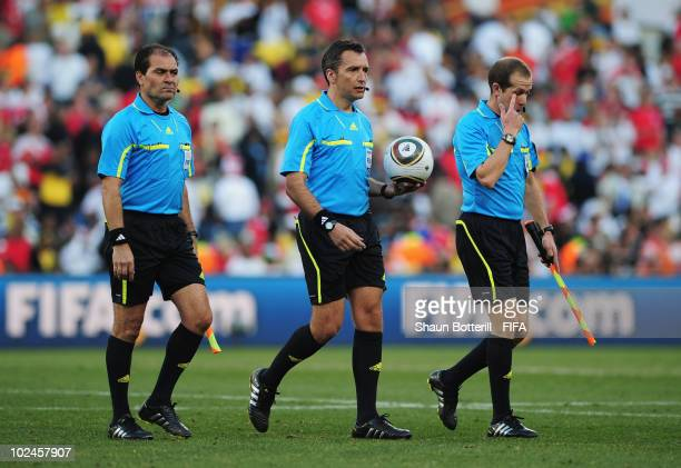 The referee Jorge Larrionda leaves the pitch at halftime with linesmen Pablo Fandino and Mauricio Espinosa during the 2010 FIFA World Cup South...
