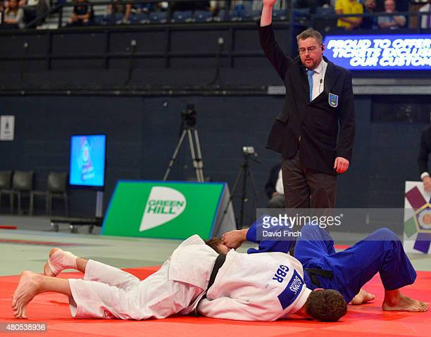 The referee lifts his arm high to signal ippon after Andrew Burns held Frazer Chamberlain to win the u90kg bronze medal during the 2015 London...
