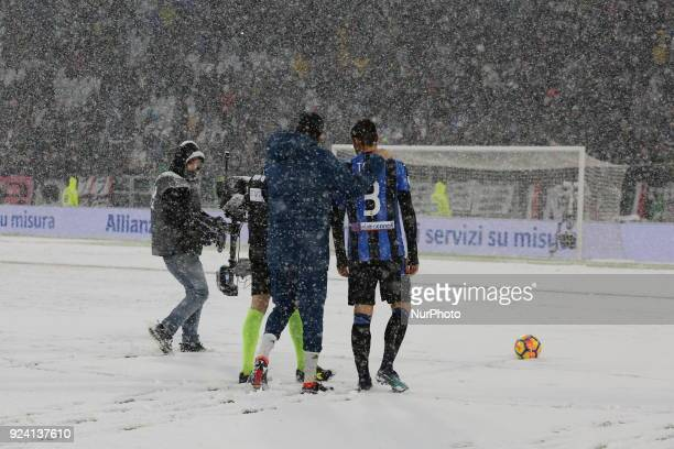 The referee Maurizio Mariani, accompanied by captains Gianluigi Buffon and Rafael Toloi tries to bounce the ball on the Allianz Stadium field on...