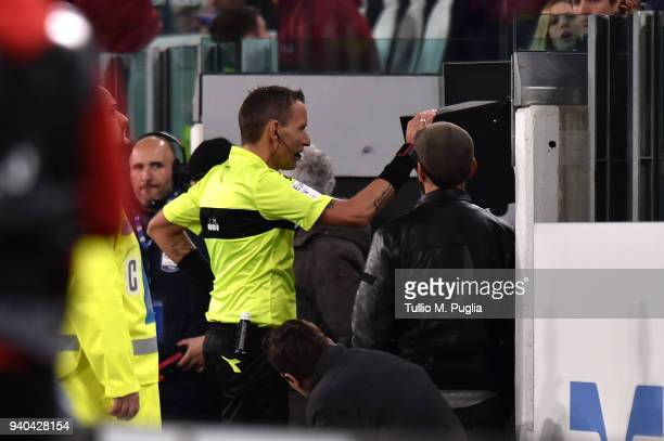 the referee Paolo Silvio Mazzoleni looks at the VAR during the serie A match between Juventus and AC Milan at Allianz Stadium on March 31 2018 in...