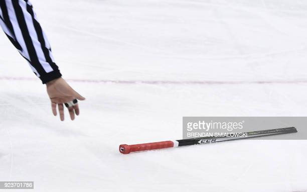 The referee picks up a broken stick in the men's bronze medal ice hockey match between the Czech Republic and Canada during the Pyeongchang 2018...