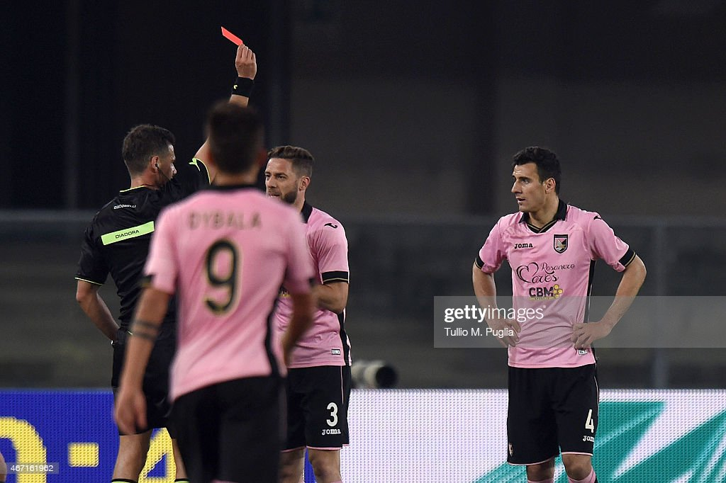 The referee Piero Giacomelli gets a red card to Sinisa Andelkovic of Palermo (R) during the Serie A match between AC Chievo Verona and US Citta di Palermo at Stadio Marc'Antonio Bentegodi on March 21, 2015 in Verona, Italy.