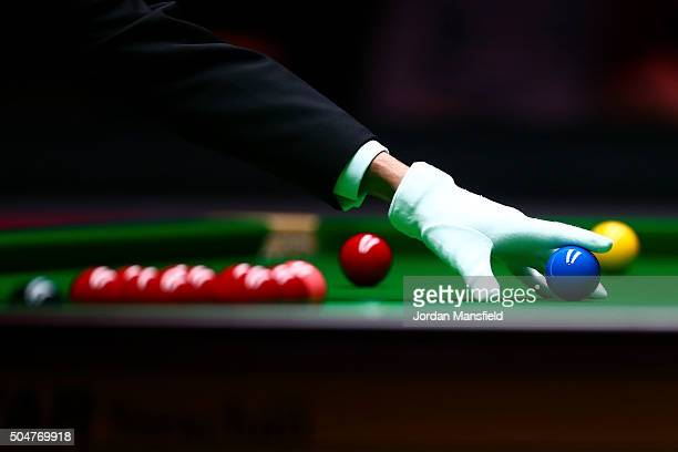 The referee places the blue ball on the cloth during the first round match between Liang Wenbo of China and John Higgins of Scotland during Day Four...