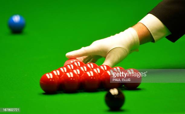 The referee places the pink ball above the reds ahead of a frame between Ding Junhui of China and Barry Hawkins of England in their quarterfinal...