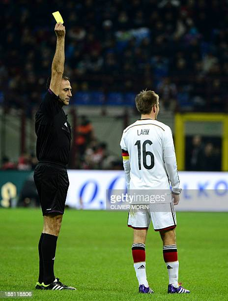 The referee raises a yellow card next to Germany's defender and captain Philipp Lahm during the 2014 FIFA World Cup friendly football match Italy vs...
