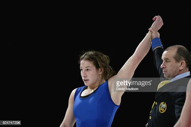 The referee raises the arm of Sara McMann signaling her victory over Canada's Trish Liebel during the women's wrestling competition at the Titan...