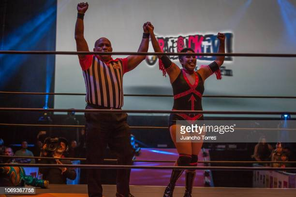 The referee raises the hand of AAA female wrestler Faby Apache in victory during an AAA World Wide Wrestling match on November 16 2018 in Bogota...