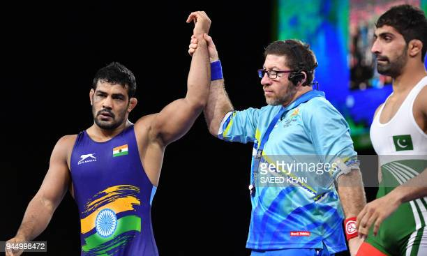 The referee raises the hand of the winner India's Kumar Sushil against Pakistan's Muhammad Asad Butt after the men's freestyle 74 kg wrestling match...