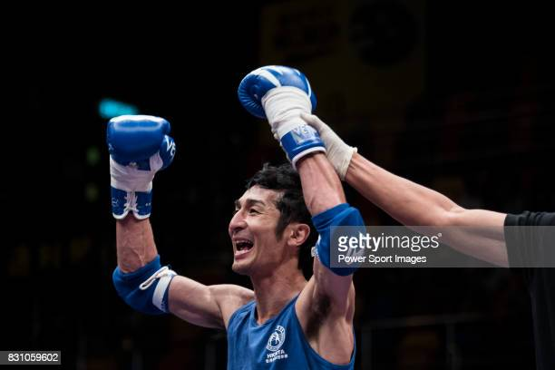 The referee rises the arm of Nitamizu Toshiyuki of Japan as he wins the gold medal in the male muay 57KG division weight bout during the East Asian...