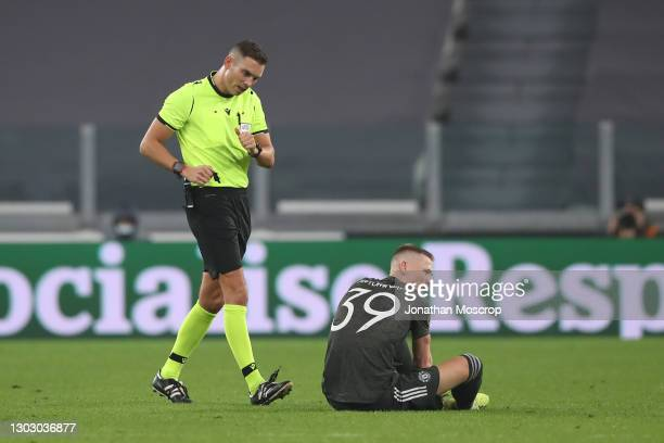 The referee Sandro Scharer of Switzerland checks on Scott McTominay of Manchester United as he sits on the pitch after picking up an injury during...