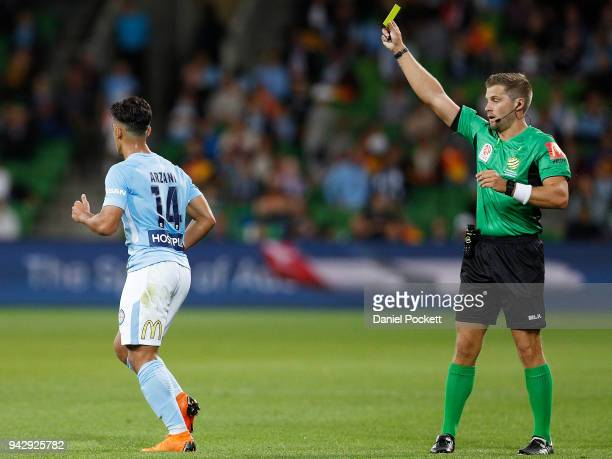 The referee shows Daniel Arzani of Melbourne City a yellow card during the round 26 ALeague match between Melbourne City and the Central Coast...