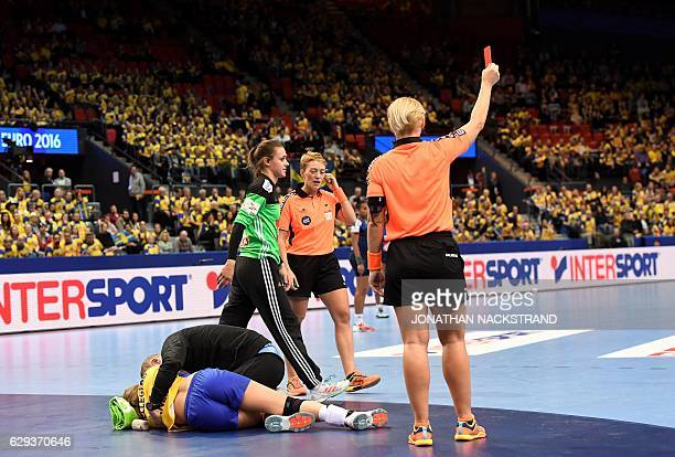 the referee shows France's goalkeeper Laura Glauser the red card during the Women's European Handball Championship Group I match between Sweden and...