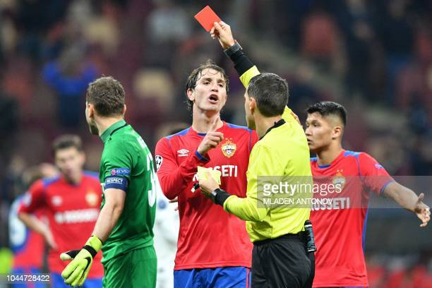 The referee shows the red card to CSKA Moscow's Russian goalkeeper Igor Akinfeev during the UEFA Champions League group G football match between PFC...