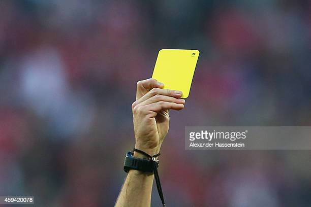 The referee shows the yellow card during the Bundesliga match between FC Bayern Muenchen and 1899 Hoffenheim at Allianz Arena on November 22 2014 in...