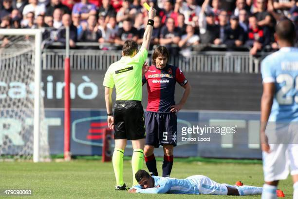 The referee shows the yellow card to Daniele Conti of Cagliari during the Serie A match between Cagliari Calcio and SS Lazio at Stadio Sant'Elia on...