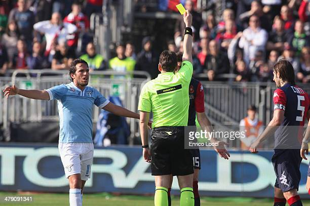 The referee shows the yellow card to Luca Rossettini of Cagliari during the Serie A match between Cagliari Calcio and SS Lazio at Stadio Sant'Elia on...