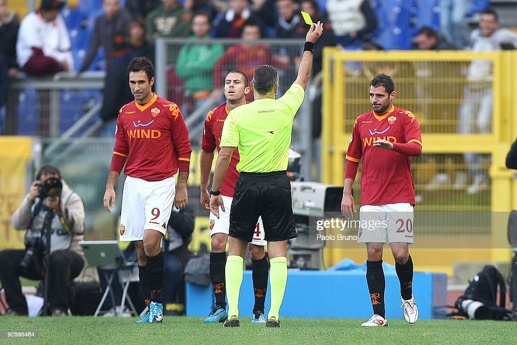 The referee shows the yellow card to Simone Perrotta (R) of AS Roma after his celebrations for the second goal during the Serie A match between AS Roma and Bologna FC at Stadio Olimpico on November 1, 2009 in Rome, Italy.