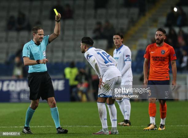 The referee shows yellow card to Nadiem Amiri of Hoffenheim during the UEFA Europa League Group C soccer match between Medipol Basaksehir and...