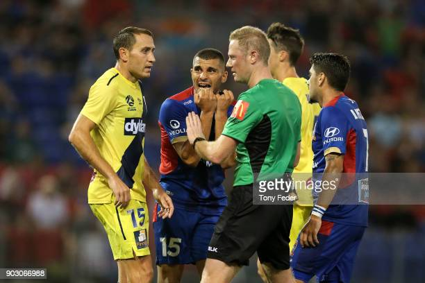 The referee talks to Alan Baro of the Mariners and Andrew Nabbout of the Jets during the round 15 ALeague match between the Newcastle Jets and the...