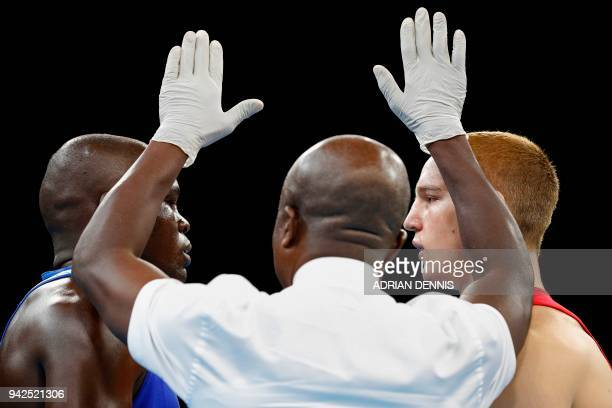 The referee talks to fighters Scotland's Scott Forrest and Kenya's Elly Ochola during the mens heavy category preliminary boxing match during the...