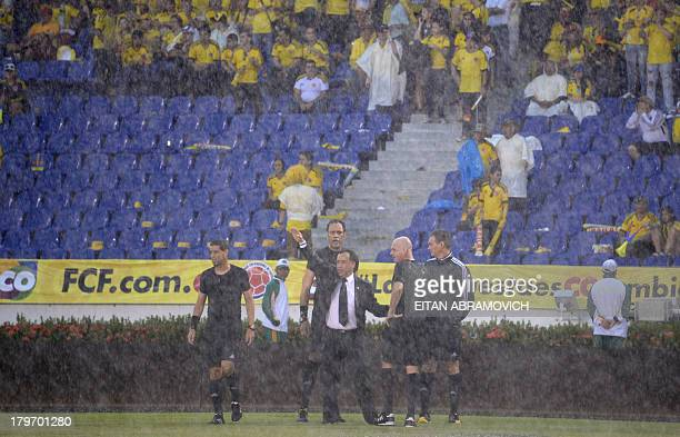 The referees and football officials wait on the field during a heavy downpour before the start of the Brazil 2014 FIFA World Cup South American...