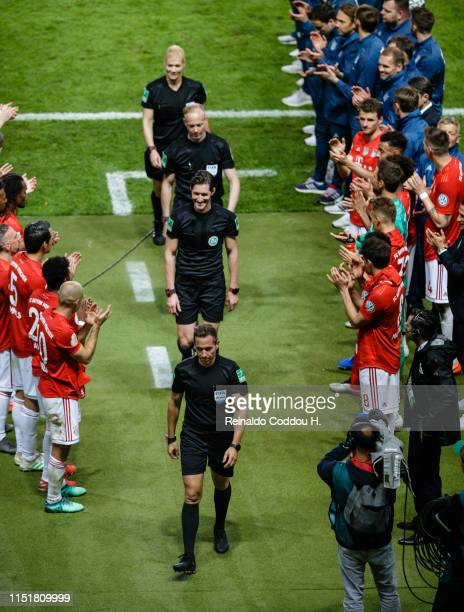 The referees are applauded by the players and staff of Bayern Muenchen after the DFB Cup final between RB Leipzig and Bayern Muenchen at...