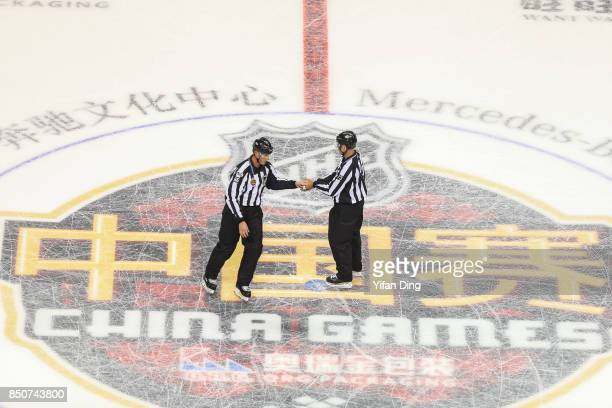 The referees react during a preseason National Hockey League game between the Vancouver Canucks and the Los Angeles Kings at MercedesBenz Arena on...