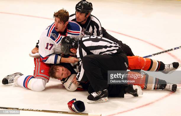 The referees try to separate Corey Perry of the Anaheim Ducks after Perry gets taken down to the ice by Brandon Dubinsky of the New York Rangers...