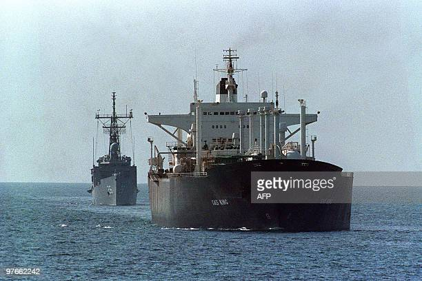 The reflagged tanker Gas King loaded with Kuwaiti crude is escorted December 28 1988 by the US guided missile frigate USS Gallery towards the Strait...
