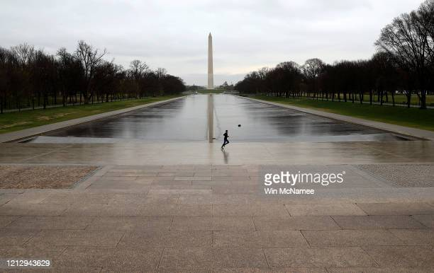 The reflecting pool and National Mall normally filled with tourists is shown nearly empty due to the impacts of coronavirus on March 17 2020 in...